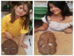 2 students making african masks